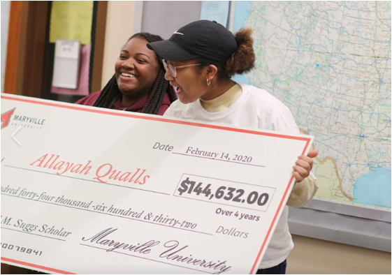 Two students stand holding a large check