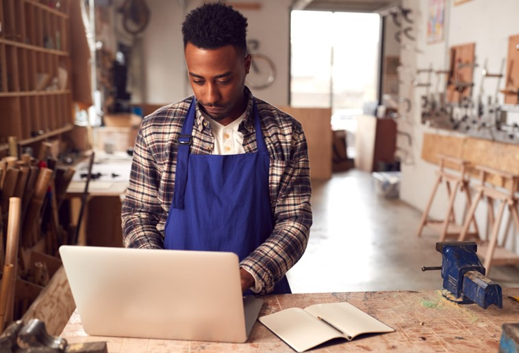 African American man stands looking at computer inside wood shop