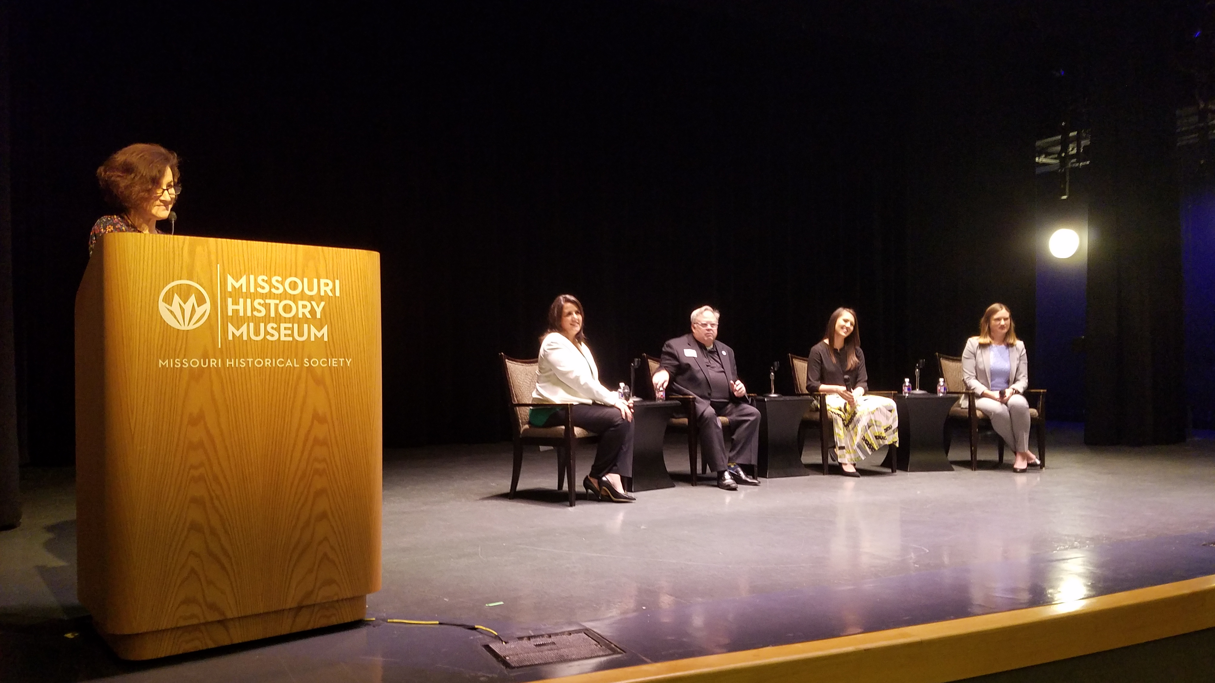 Four people sitting on a stage and one person standing at podium