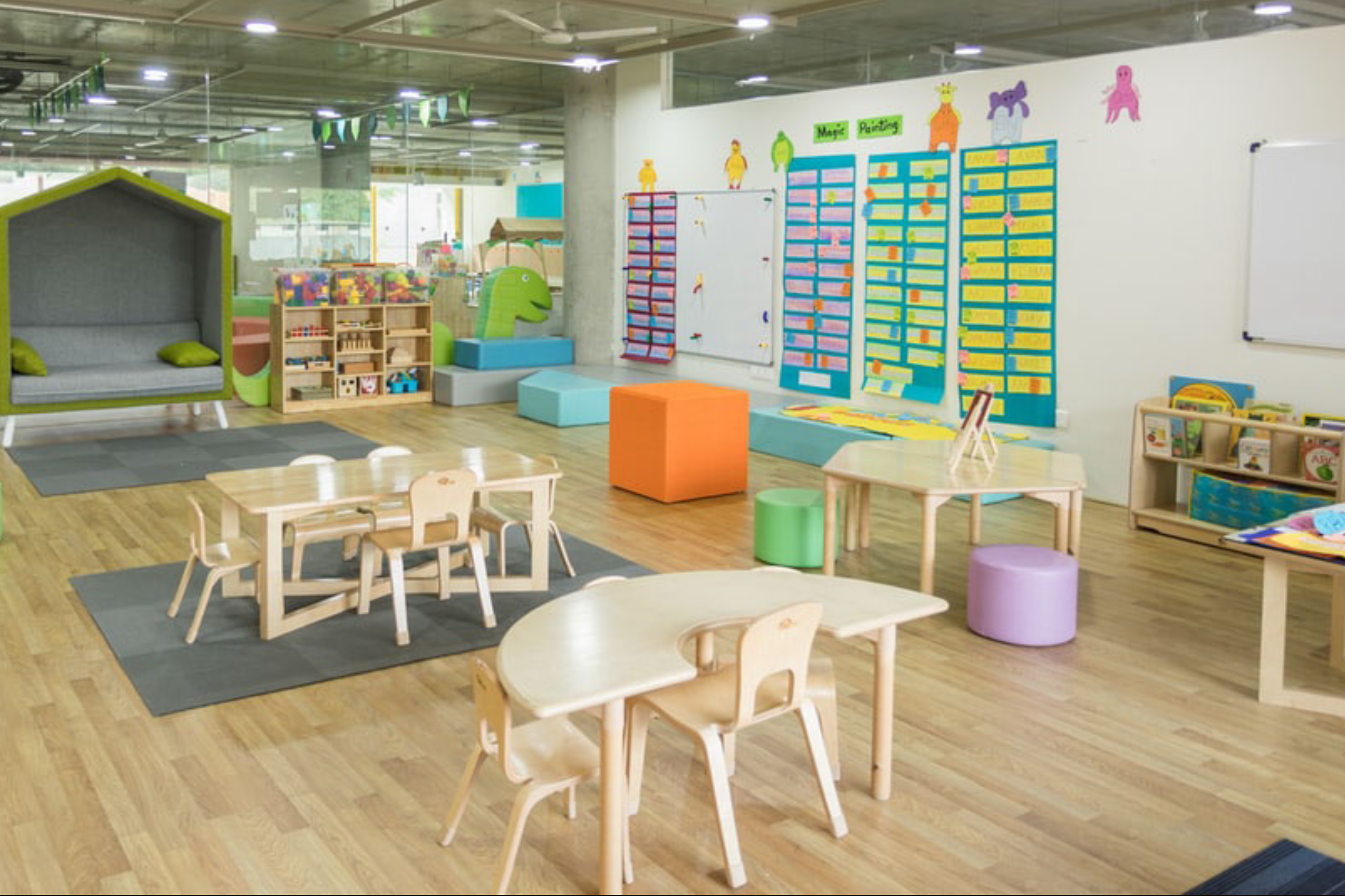 Pre-K classroom with tables, chairs, and learning materials on the wall