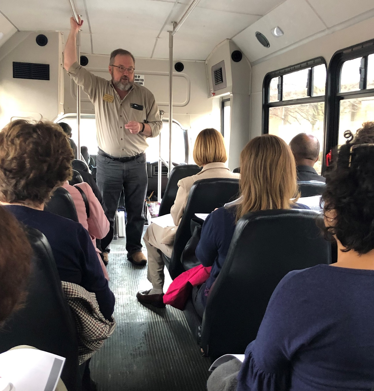 Andy Theising standing on bus talking to seated funders