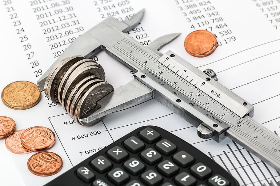 Image of a calculator, some loose change, and a ruler